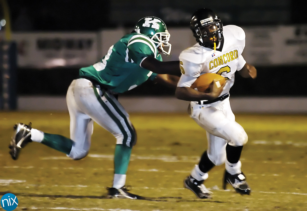Concord's Tony Moore tries to avoid a tackle from A.L. Brown's Chris Moore Friday night at Kannapolis Memorial Stadium.