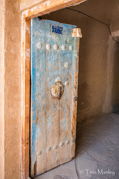 Old, blue wooden door with knocker leading into traditional restaurant in Abarkuh, Iran.