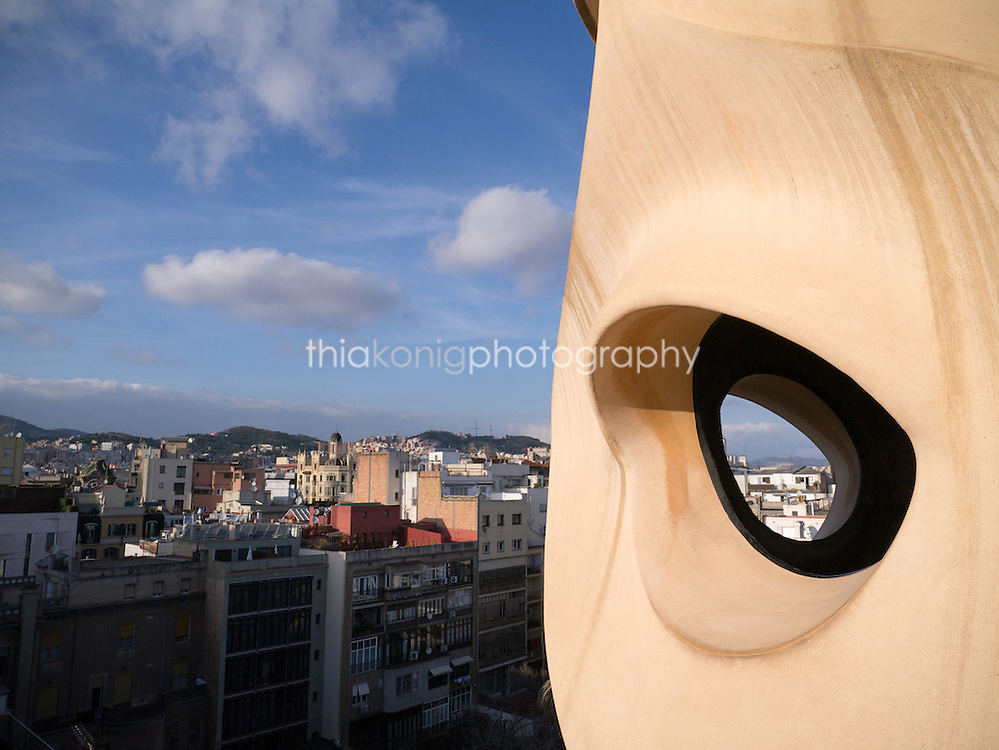 Looking out through an artistic chimney sculpture on the roof of Casa Mila, designed by Gaudi in Barcelona, Spain.