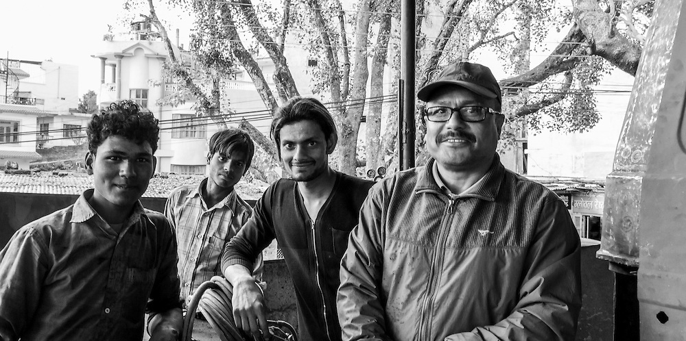 Four workers at an auto body shop in Tansen, Nepal pose for a photograph