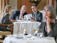 Three business people sitting at table in restaurant analyzing documents