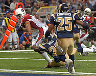 Arizona Cardinals wide receiver Larry Fitzgerald (11) fights his way into the end zone past St. Louis defensive back Tye Hill (26) and Corey Chavous (25) in the first half, at the Edward Jones Dome in St. Louis, Missouri, December 3, 2006.  The Cardinals beat the Rams 34-20.<br />