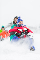 Excited young friends sledding in snow