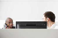 Two office workers sitting in office cubicle one using phone