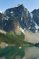 Canoeists paddling on Moraine Lake with the Wenkchemna Peaks towering above Banff National Park Alberta Canada