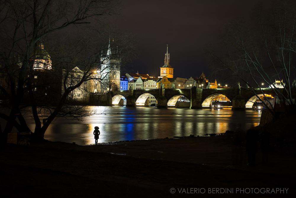 Looking at Charles Bridge at night from the banks of Vltava River