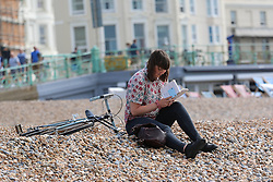 © Licensed to London News Pictures. 14/06/2014. Brighton, UK. A woman reason a book on the beach. Brighton is readying itself for the flood of sun seekers and holiday makers. The weekend is expected to be the hottest of the year so far with temperatures reaching close to 30C down the south coast. Photo credit : Hugo Michiels/LNP