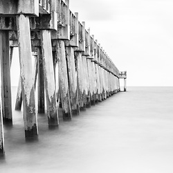 Pensacola Beach Florida Gulf Pier black and white panorama photo. Pensacola Beach is on Santa Rosa Island in the Emerald Coast region of the Southeastern United States of America. Panoramic photo ratio is 1:3. Copyright ⓒ 2018 Paul Velgos with All Rights Reserved.