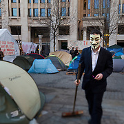 An activist clean the sqaure wearing an Anonymous mask. Activists all over the world have taken on the mask, modelled on Guy Fawkes and the film character V in defiance of the establishment. The camp Occupy London Stock Exchange outside St Paul's Cathedral was in the morning served with eviction notice after months of legal battle with the Corporation of London. The site was occupied Oct 15th.