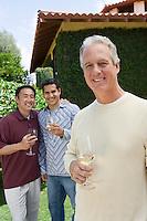 Three male friends drinking wine in garden, portrait