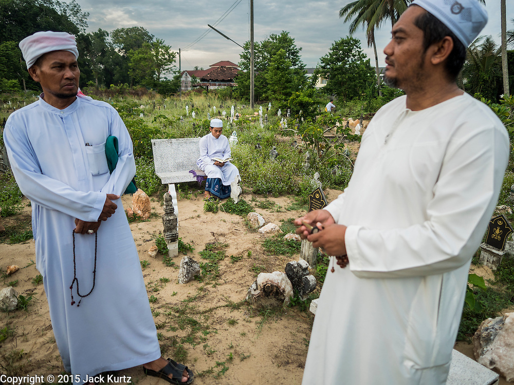 19 JUNE 2015 - PATTANI, PATTANI, THAILAND: Thai Muslim men chat while a teenager prays behind them in Perkuboran To'Ayah, the Muslim cemetery in Pattani. It is more than 150 years old. The last Sultan of Pattani, who ruled until Siam (Thailand) annexed Pattani is buried in the cemetery. Many victims of political and sectarian violence that has wracked Thailand's three Muslim majority provinces, Pattani, Narathiwat and Yala are also buried in the cemetery. On Fridays, after morning prayers, Muslim men come to the cemetery to tend to the graves of their family members.   PHOTO BY JACK KURTZ