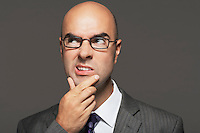Bald businessman wearing glasses with hand on chin making funny face