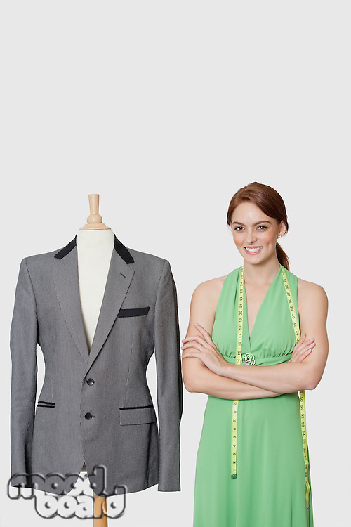 Portrait of female dressmaker standing next to tailor's dummy over gray background