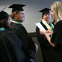 Counselor Casey Poole makes sure she says Trevor Buse's name correctly for when he receives his diplomab efore the start of Mooreville High School's graduation ceremony Saturday afternoon at the BancorpSouth Arena.