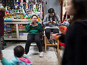 29 FEBRUARY 2020 - ST. PAUL, MINNESOTA: People walking by girls playing on their smart phones in front of their family's shop in the Hmong Village. Thousands of Hmong people, originally from the mountains of central Laos, settled in the Twin Cities in the late 1970s and early 1980s. Most were refugees displaced by the American war in Southeast Asia. According to the 2010 U.S. Census, there are now 66,000 ethnic Hmong in the Minneapolis-St. Paul area, making it the largest urban Hmong population in the world. Hmong Village, the largest retail and restaurant complex that serves the Hmong community, has more than 250 shops and 17 restaurants.   PHOTO BY JACK KURTZ
