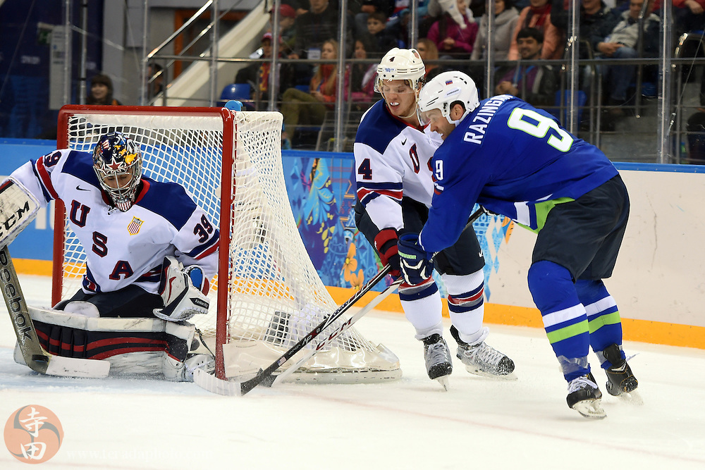 Feb 16, 2014; Sochi, RUSSIA; Slovenia forward Tomz Razingar (9) attempts a wrap around shot against USA goalie Ryan Miller (39) and defenseman John Carlson (4) in a men's ice hockey preliminary round game during the Sochi 2014 Olympic Winter Games at Shayba Arena.