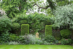 Trellis boundary fence covered with planting in order to 'borrow' neighbouring trees. Stone lion statue as focal point