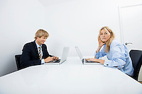 Portrait of businesswoman with coworker working in office
