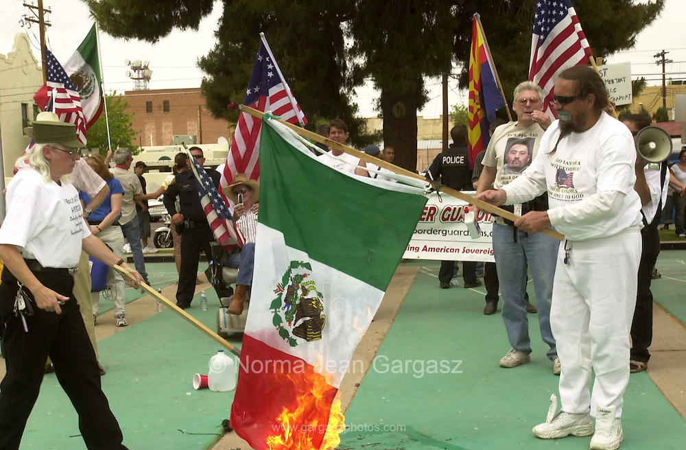 Counter protestors, Laine Lawless, (left), and Russ Dove, burn the flag of Mexico at Armory Park, which served as the destination for thousands who marched in protest of propsed immigration legislation, on April 10, 2006, In Tucson, Arizona, USA.  Roy Warden, (second from right), stands back.