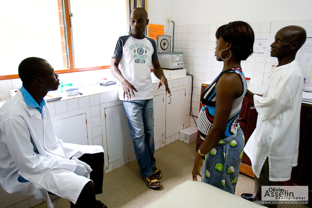 Aya Solange Siallo, 24, meets with HIV/AIDS counselor Kevin Kouassi Gallet and lab technicians Kwasi Koffi Jacques, left, and Éttie Koffi, right before getting tested for HIV/AIDS at the NDA health center in Dimbokro, Cote d'Ivoire on Friday June 19, 2009.