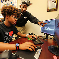 Allen Pegues Sr, helps his son Allen Jr., with some suggestions while he edits a video for one of their customers.