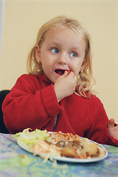 Young girl sitting at table eating lunch,