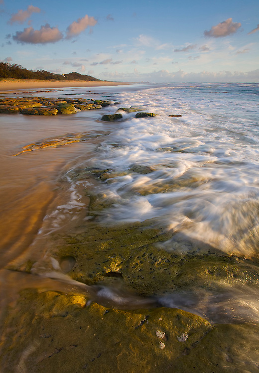 The milky wash of the Pacific Ocean gently engulfs the rock littered shoreline early one morning in Wurtulla.