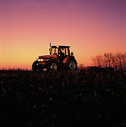 A modern farm tractor works a field into the late evening hours.
