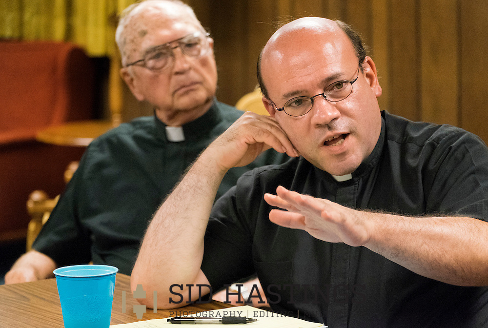 28 JULY 2015 -- ST. CHARLES, Mo. -- The Rev. Mark Whitman (right) participates in a meeting of clergy and staff at St. Robert Bellarmine Catholic Church in St. Charles, Mo., Tuesday, July 27, 2015. The Rev. Whitman  is teaming with Deacon John Schiffer to lead the parish following the departure of previous pastor The Rev. Patrick Ryan. Also pictured is Monsignor Ray Hampe (left), in residence at St. Robert Bellarmine.  Photo © copyright 2015 Sid Hastings.