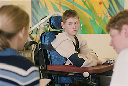 Young boy with cerebral palsy sitting in wheelchair watching female doctor talk to mother on Children's ward of hospital,