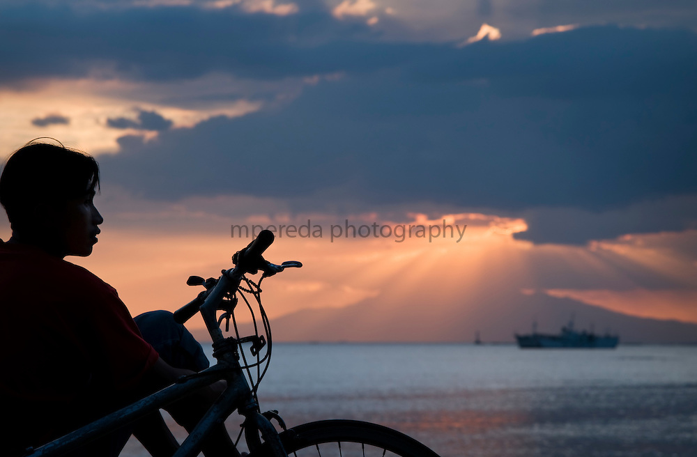 MANILA (Philippines). 2009. A boy watching the sunset in Manila´s bay from Roxas Bulevard