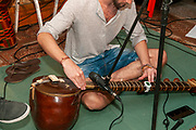Young Sitar player tunes his instrument