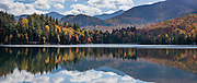Heart Lake, Adirondacks. Hike Mount Jo in the Adirondack Mountains, near Lake Placid, North Elba, New York, USA. Beautiful Heart Lake and Adirondak Loj (an historic lodge) lie at the foot of Mount Jo (2876 ft or 877 m elev), which is on land owned by the Adirondack Mountain Club (AMC). With a sweeping vista of the Great Range, Mt Jo offers one of the best views for the effort in the Adirondacks: ascend 710 feet or 216 m from the Loj in 2.6 miles roundtrip. From atop Mt. Jo, see the surrounding High Peaks Wilderness Area, a state Forest Preserve protected within Adirondack Park. Adirondack Park is the largest park in the contiguous USA and is the largest National Historic Landmark. Geologic history: The Adirondacks are very new mountains from old rocks, uplifting in a circular dome (160 miles wide and 1 mile high) over just the past 5 million years. Geologically, the Adirondacks are NOT in the Appalachians: instead, they are part of the Canadian Shield (or Laurentian or Precambrian Shield which underlies half of Canada). The Adirondacks are still rising fast, up to 3 mm per year, with a central core (High Peaks region) of intrusive igneous rock, Anorthosite (not common at Earth's surface but common on the Moon's surface), surrounded by a massive dome of 1-billion-year-old metamorphic gneiss rock, in turn surrounded by some younger sedimentary rocks. In contrast, the unrelated Appalachians have mostly younger sedimentary rocks, yet are among the world's oldest mountains and are no longer uplifting. The panorama was stitched from 3 overlapping photos.