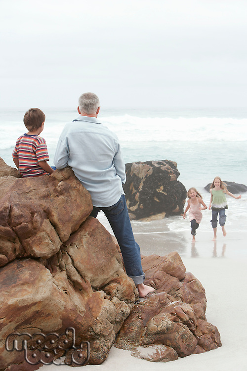 Father with Children on Rocky Beach