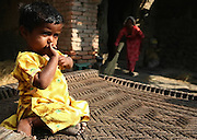 A baby sits on a charpoy (a woven bed), while her mother cleans the house behind her in Khairo Dero village, in Larkana, Pakistan, on Thursday, Jan. 24, 2008. Pakistan is seeking to sustain growth in a country where the government estimates a fourth of the population lives in poverty, or on less than a dollar a day.