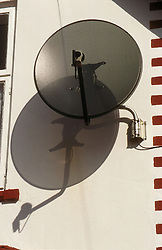 Satellite dish positioned on side of house,