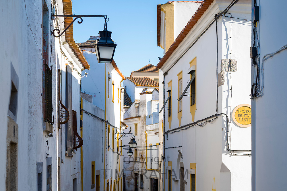 Typical white and yellow houses in narrow street in Evora, Portugal