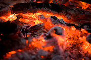 Close up of charcoal embers and ash from a fire glowing red hot with a shallow focus depth of field..