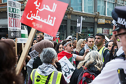 London, UK. 30th March, 2019. Pro-Palestinian campaigners attending a Rally for Palestine outside the Israeli embassy to demand freedom, justice and equality for the Palestinian people stand in front of a small pro-Israel counter-protest