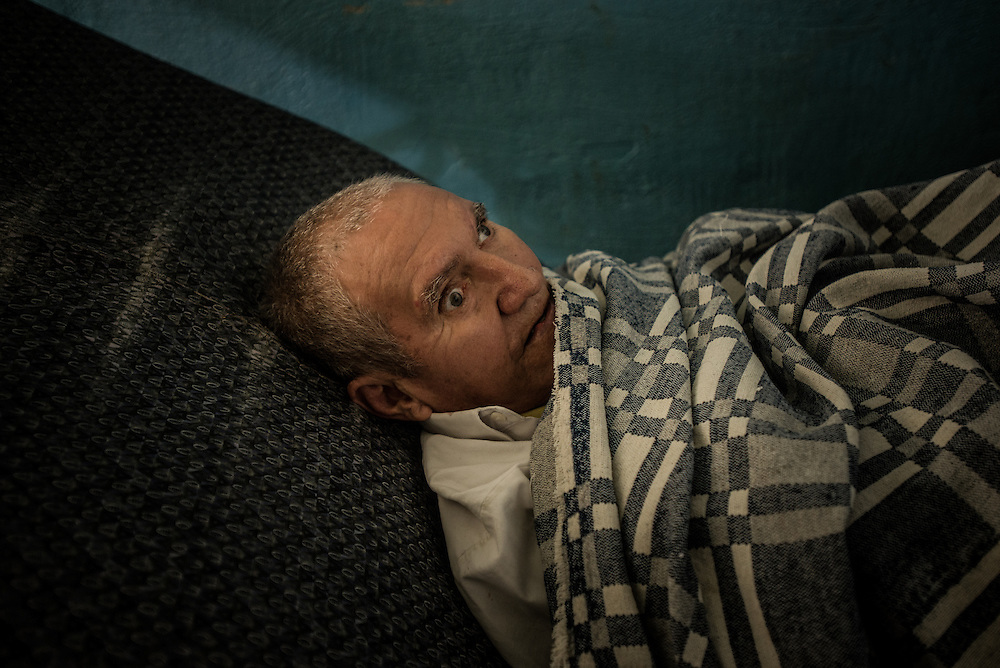 "BARQUISIMETO, VENEZUELA - JULY 28, 2016: Guillermo Salazar rests in his hospital bed. Salazar is a patient at El Pampero psychiatric hospital that suffers from a mental impairment consequential of drug abuse.  His roommate at the hospital recently died, and Salazar cries every day because he misses him. ""I don't like to be alone,"" he said. The economic crisis that has left Venezuela with little hard currency has also severely affected its public health system, crippling hospitals like El Pampero Psychiatric Hospital by leaving it without the resources it needs to take care of patients living there, the majority of whom have been abandoned by their families and rely completely on the state to meet their basic needs. PHOTO: Meridith Kohut"