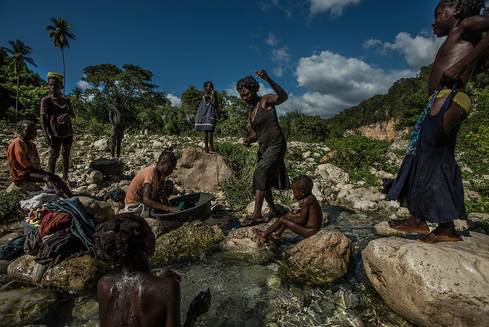 TETE A L'EAU, HAITI - NOVEMBER 22, 2015: Families bathe and wash clothes in the river that runs next to Camp Tete A L'eau. On this arid strip of borderland, the river brings life. Its languid waters cook the food, quench the thirst and bathe the bodies of thousands of Haitians who poured onto its banks this summer, fleeing threats of violence and deportation from their neighbors in the Dominican Republic.  These days, it is also brings death. Horrid sanitation has lead to a cholera outbreak in the camps, infecting and killing residents. PHOTO: Meridith Kohut for The New York Times