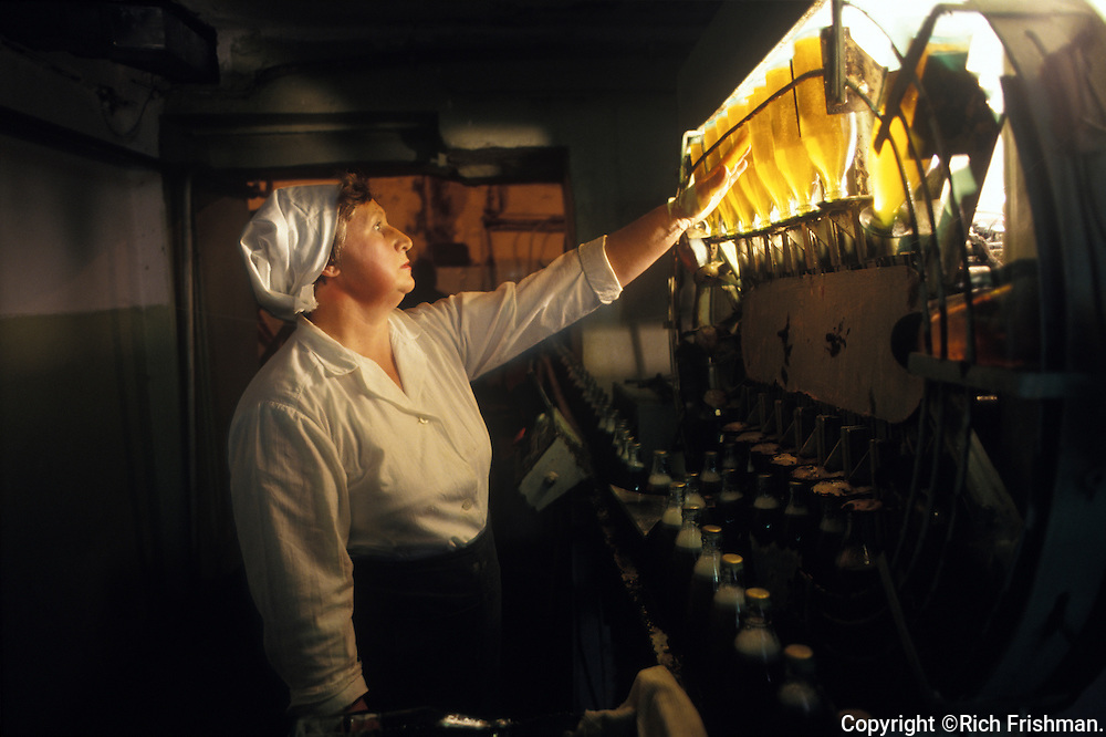 Photograph of woman inspecting beer bottles on conveyor belt in brewery bottling plant in Russian Far East City of Sovetskaya Gavan; Khabarovsk Krai Russia.©Rich Frishman.