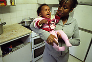 Girl holding her baby daughter in the kitchen of a flat in housing estate Lambeth Walk South London c.2000
