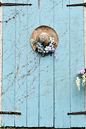 Closeup of picturesque Cape Cod barn door with decorated straw hat on door.