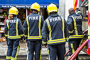 Firefighters from the London Fire Brigade respond to an emergency on Church Street, Stoke Newington, London.  They have been called out due to an explosion in the basement of a shop.  The London Fire Brigade is the 4th largest fire-service in the world.  The firefighter on the left of the image is a woman. As of 2012 there are 257 female firefighters in the London Fire Brigade.  As of March 2007 the proportion of operational firefighters in the UK who were women was 3.1%.