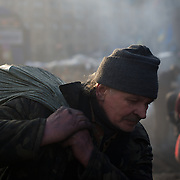 KIEV, UKRAINE - February 20, 2014: An anti-government protestor carries bags filled with burned debris, to be used in the formation of barricades, as violent clashes happen between protestors and police outside Independence Square in central Kiev. The riot police responded to the advance with gunfire that, according to the opposition, killed at least 70 and as many as 100 people. The drastic escalation of the three-month-old Ukraine crisis left the country reeling from the most lethal violence in decades. CREDIT: Paulo Nunes dos Santos