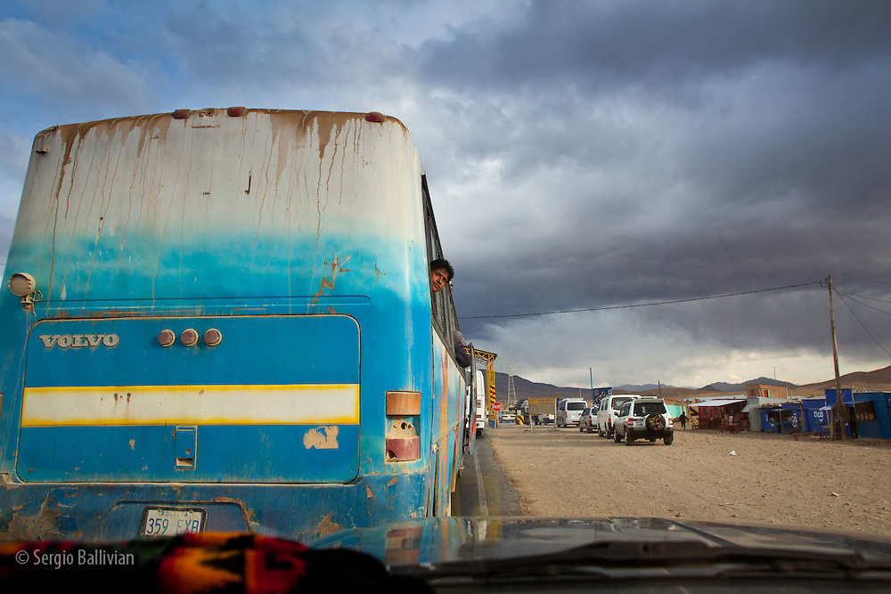 A passenger peeks out from a local bus that transports people to all corners of the Bolivian Altiplano.