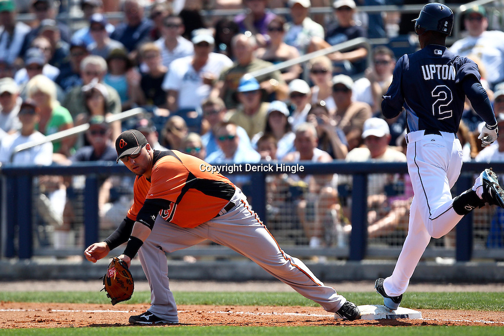 March 20, 2011; Port Charlotte, FL, USA; Baltimore Orioles catcher Jake Fox (9) makes the catch for an out against Tampa Bay Rays center fielder B.J. Upton (2) during a spring training exhibition game at Charlotte Sports Park.   Mandatory Credit: Derick E. Hingle