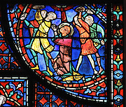 Three executioners hurl rocks at St Stephen and a fourth man, on the right, collects the rocks and hands them to them. St Stephen kneels and prays to God, forgiving his murderers for their sin. A beam of light shines on his bloody face. Section of the stoning of St Stephen, 1220-25, from the Life of St Stephen and transferral of his relics window in the ambulatory of Chartres Cathedral, Eure-et-Loir, France. This window, unusually dominantly red in colour, tells the story of the life of St Stephen, the first Christian martyr, who died c. 36 AD and whose relics are held at Chartres. It is situated in the chapel dedicated to martyrs. Chartres cathedral was built 1194-1250 and is a fine example of Gothic architecture. Most of its windows date from 1205-40 although a few earlier 12th century examples are also intact. It was declared a UNESCO World Heritage Site in 1979. Picture by Manuel Cohen