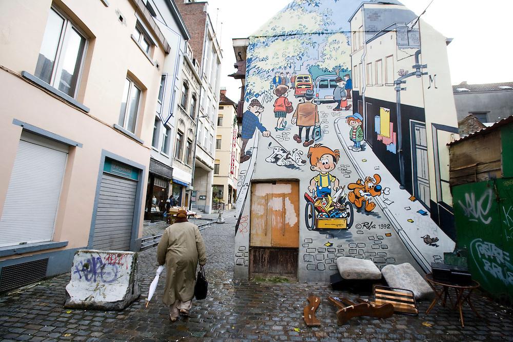 BRUSSELS - BELGIUM - 21 OCTOBER 2008 -- A woman on Rue du Chevreuil passes a wall paint showing a belgian comics strip near the flea-marked Jeu de balle. Photo: Erik Luntang